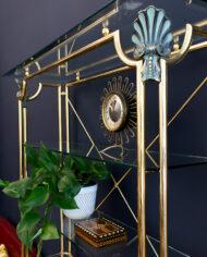Hollywood Regency messing wandkast met marmeren onderplaat, glazen schappen en schelpdecoraties